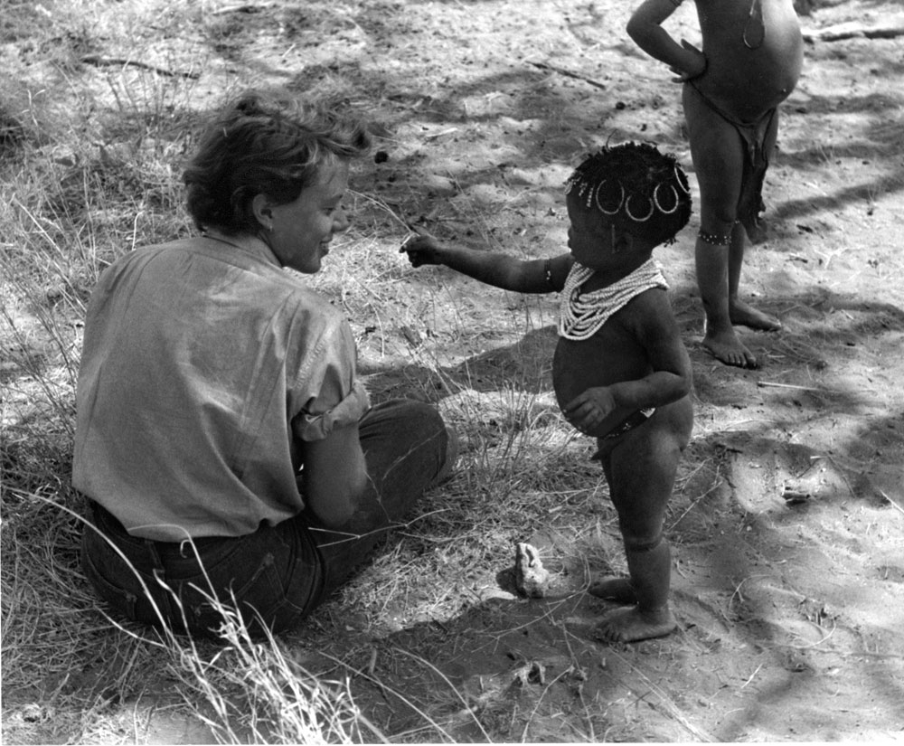 Elizabeth, being offered a caterpillar from San/Bushman child